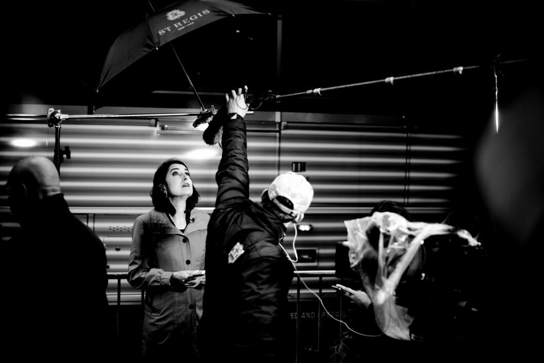 TRUMP TOWER, 9. NOVEMBER 2016 - KL 13.53: Kameramannen justerer lyset og mikrofonen for reporteren mens en buss i bakgrunnen kjører forbi i bakgrunnen. En paraply fra luksushotellet St. Regis beskytter mot pjuskregnet.