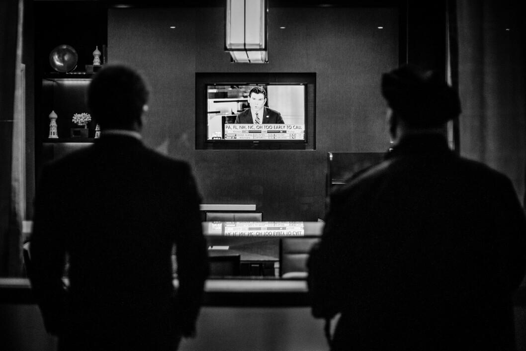HILTON MIDTOWN, 8. NOVEMBER 2016 - KL 20.37: En mann jeg tror er Secret Service-agent og en mann jeg er bra sikker er politimann ser på Fox News på en TV-skjerm inne på Midtown Hilton. Det er for tidlig å kåre en vinner i de fleste vippestater, men Donald Trump gjør det bedre enn forventet.