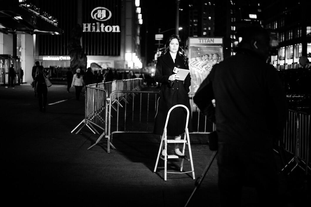 HILTON MIDTOWN, 8. NOVEMBER 2016 - KL 21.21: Alt for å oppnå den perfekte komposisjon. En kvinnelig reporter - som mange andre reportere utenfor Hilton Midtown - bruker en stige for å stå i høyde med skilten til hotellet.
