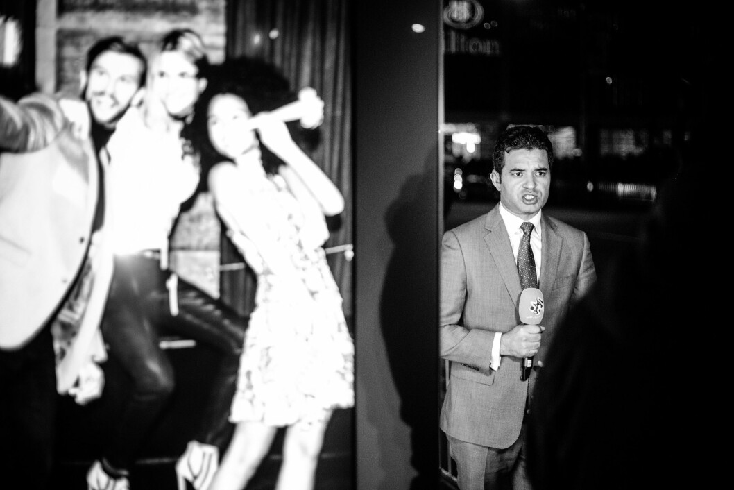 HILTON MIDTOWN, 9. NOVEMBER 2016 - KL 02.06: En reporter står like ved et busstopp med Hilton Midtown i bakgrunnen. Samtidig som det er klart at Donald Trump vil vinne presidentvalget i USA, så viser en reklameplakat lykkelige unge mennesker som tar en selfie.