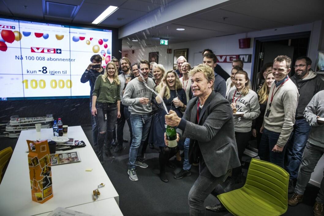 Redaksjonssjef Espen Olsen Langfeldt i VG+ spretter champagne etter at VG+ nådde 100 000 abonnenter. Målet ble nådd cirka klokken 14.45 den 1. februar 2017. Det ble feiret med kake og champagne foran storskjermen i 6. etasje i VG-bygget.