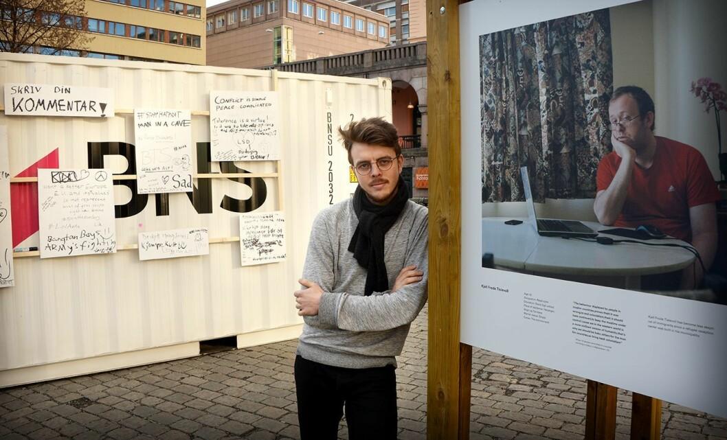 Fotograf Kyrre Lien sammen med sin utstilling på Youngstorget i Oslo.