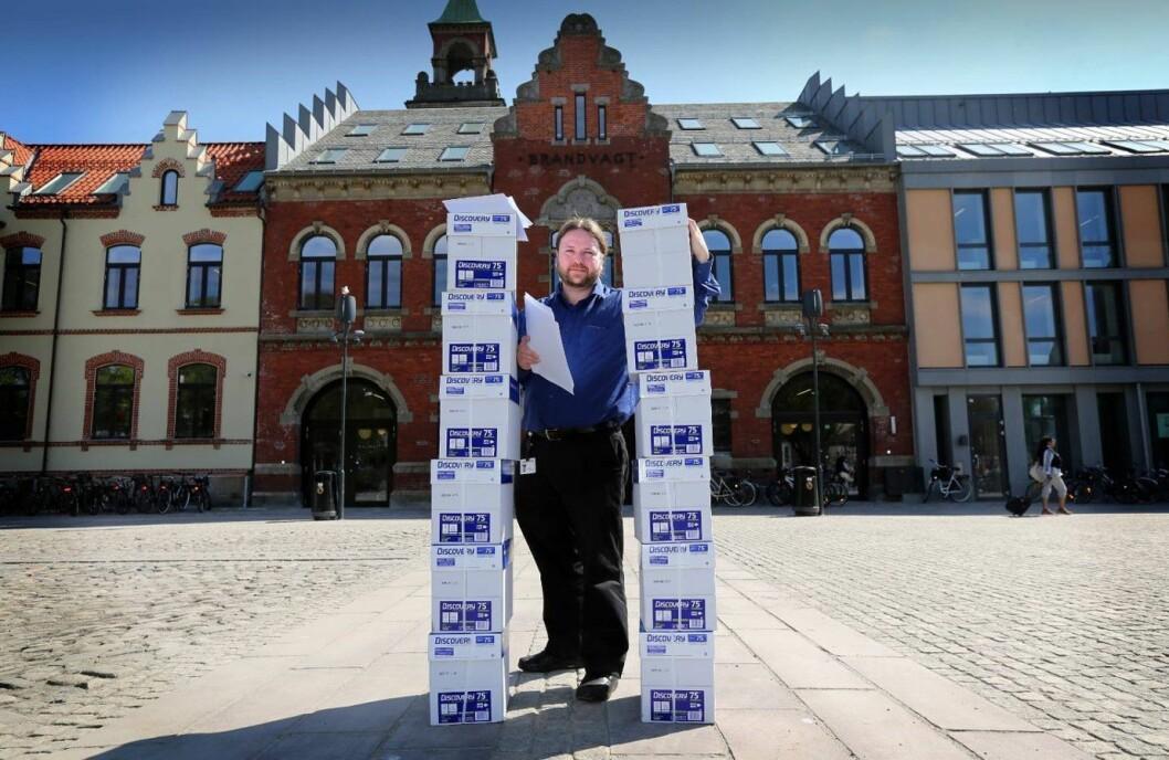 Journalist Tarjei Leer-Salvesen foran Kristiansand rådhus med papir som tilsvarer postlistene for kommunen - kun én årgang. Arkivfoto