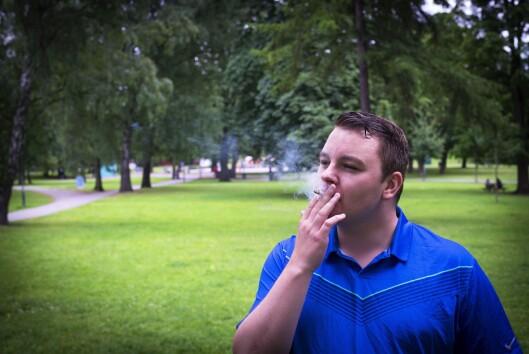 Espen Teigen tar en røyk i parken i Oslo mens han snakker om at mediene har sviktet folket.