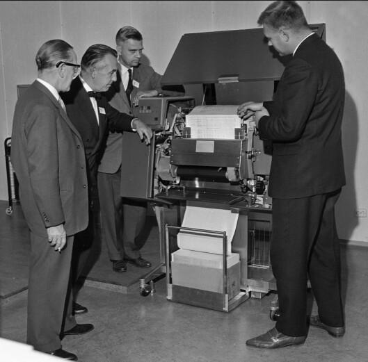 Den teknologiske utviklingen har vært rivende i NTBs historie. Her er NTBs valgredaksjon samlet rundt datamaskinen som samler inn resultater fra kommunevalget i 1963.