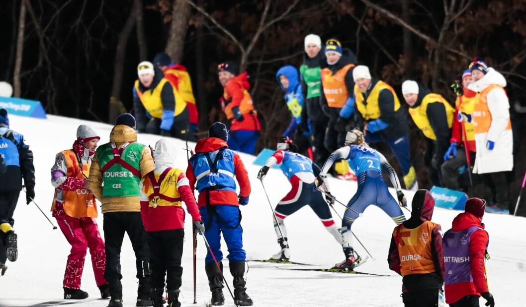 Langrenn 4x5 km. stafett kvinner i Alpensia Cross-Country Skiing Centre under vinter-OL i Pyeongchang. Marit Bjørgen (t.v.) og Stina Nilsson fra Sverige på vei opp siste bakke, der det står medlemmer av både svensk og norsk støtteapparat langs løypa.Foto: Lise Åserud / NTB scanpix