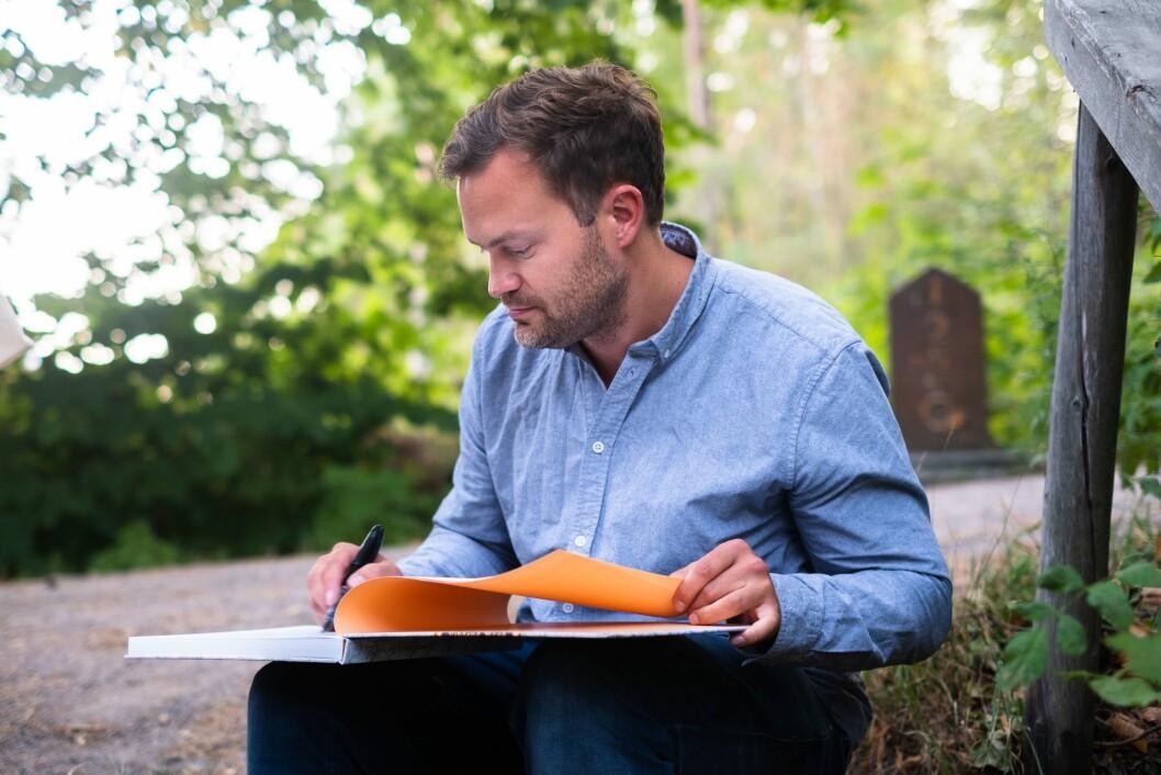 Vårt Land-fotograf Erlend Berge signerer bøker under lanseringa av «Sjå, eg kjem snart!» tirsdag. Foto: Ole Gunnar Onsøien