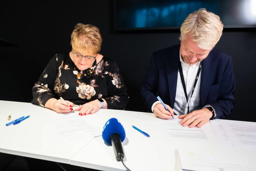 Kutlurminister Trine Skei Grande og TV 2-sjef Olav Sandnes signerer avtalen.
