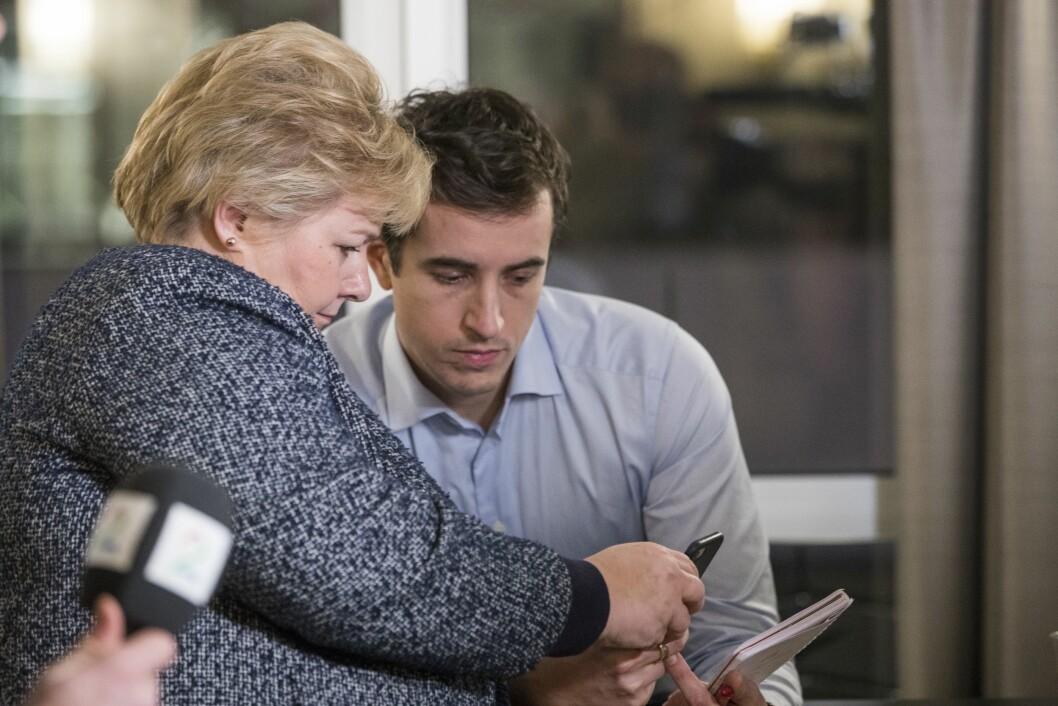 Statsminister og Høyre-leder Erna Solberg ser på mobiltelefonen til Høyres pressesjef Peder Weidemann Egseth i januar i år.