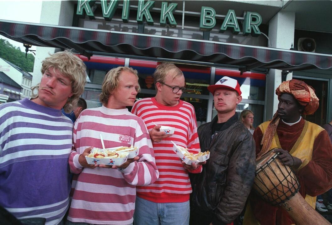 """Eia har lang fartstid fra NRK. Her fra 25. august 1995, hvor « Lille lørdag»-gjengen tester påmmfri utenfor rutebilstasjonen i Arendal. Fra venstre: Vidar ( Bård Tufte Johansen), Jan-Tore ( Harald Eia), Øistein ( Øystein Kvaalsvik), """"Djevelen fra Froland"""" og Mustaka."""