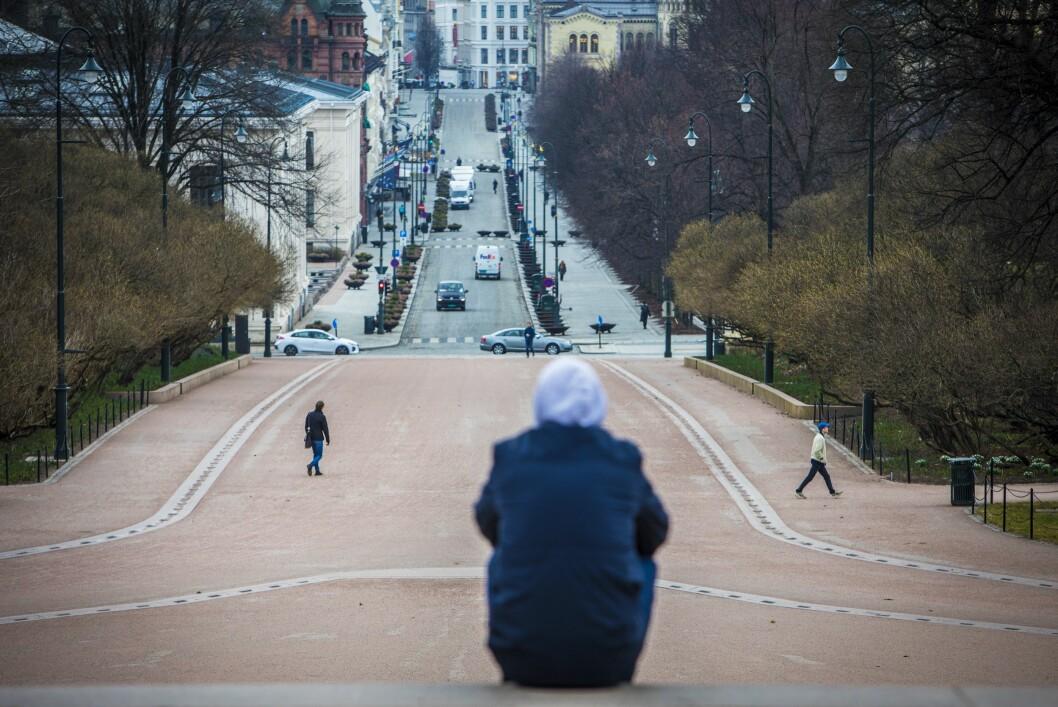 Koronaviruset setter sitt preg på Norge. Tirsdag forrige uke var det svært få mennesker ute i Oslo sentrum. En mann sitter i trappen foran Slottet og skuer ut overr et nesten folketomt Karl Johan.