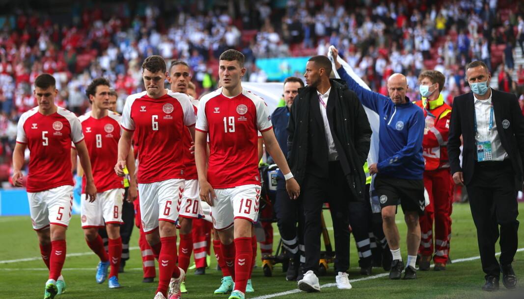 De danske spillerne eskorterer Christian Eriksen av banen etter et illebefinnende.