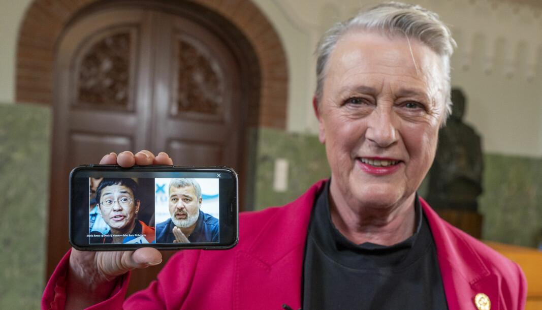 Berit Reiss-Andersen, leder av Nobelkomiteen, viser frem et bilde på en mobiltelefon av årets fredsprisvinnere, journalistene Maria Ressa og Dmitrij Muratov på Nobelinstituttet i Oslo fredag.